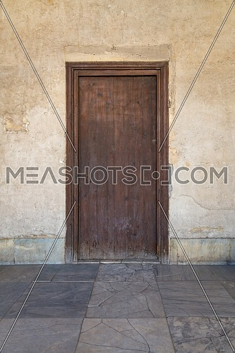 Grunge wooden aged door on weathered stone wall, Medieval Cairo, Egypt