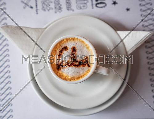 Coffee cup with foam and above the foam the inscription Cuba on a turquoise background