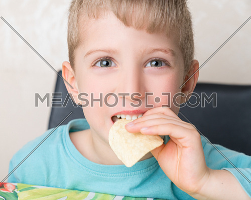 A child with pleasure eating potato chips sitting at a table on a light background. The boy is eating chips and smiling.