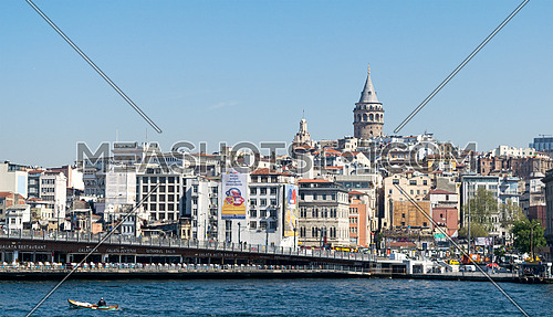 Istanbul, Turkey - April 26, 2017: City view of Istanbul, Turkey overlooking Galata Bridge with traditional fish restaurants and Galata Tower in the background