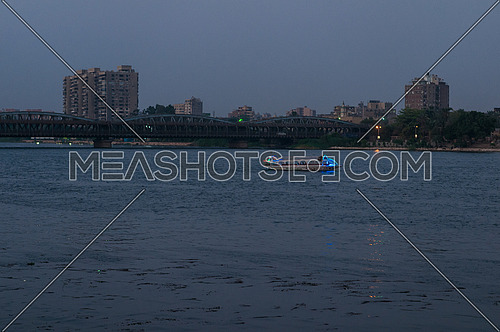Long shot for The River Nile and motor boat showing Imbaba Bridge in background at Sunset