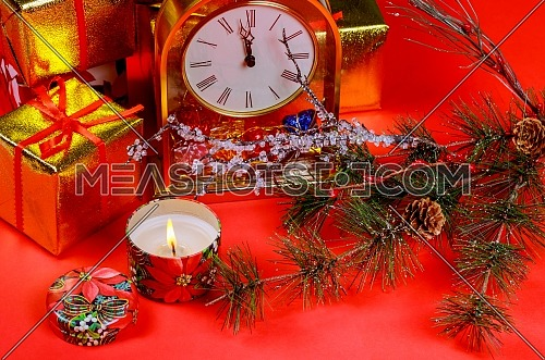Christmas composition gift boxes and decor candle light. Christmas and New year clock holidays red background