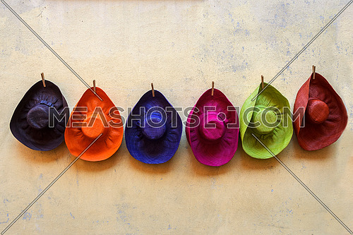6 colorful hats hanged on a wall