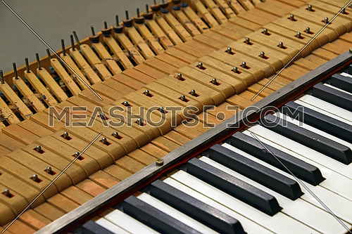 Close up tuning open old vintage piano keyboard, high angle view