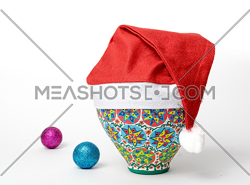 Studio shot of Egyptian decorated colorful pottery vase wearing Santa Claus red hat on white background with two colored shining Christmas balls