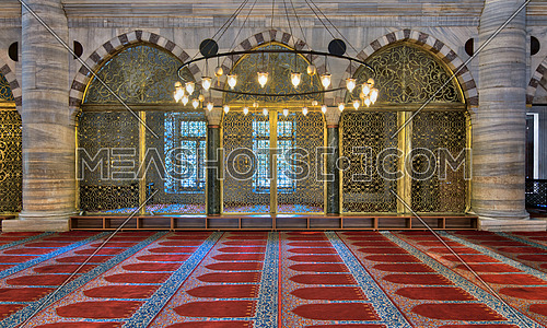 Interior shot of three arched ornate engraved golden doors, big chandelier over marble wall with pillars and red decorated carpet at Suleymaniye Mosque, Istanbul, Turkey