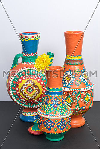 Studio shot of still life of three orange ornate pottery vases on background of black table and white wall