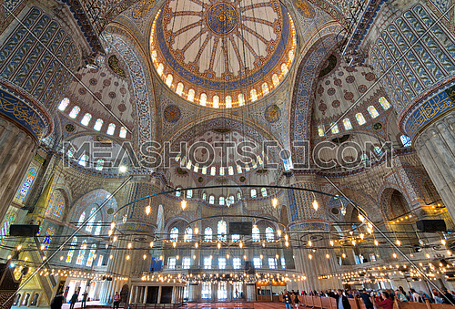 Istanbul, Turkey - April 16, 2017: Interior of Sultan Ahmed Mosque (Blue Mosque), with a huge pillars, arches, colored stained glass windows and tourists visiting the mosque, Istanbul, Turkey