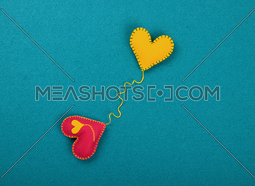 Felt craft and art, two handmade stitched toy hearts, red and yellow connected together with one thread on blue background