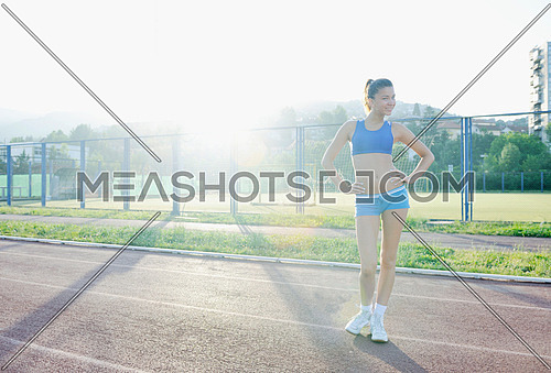 happy young woman on athletic race track relax