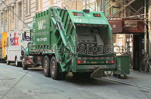 Pan Left Shot for Garbage truck parked revealing other trucks and street at New York City at day.