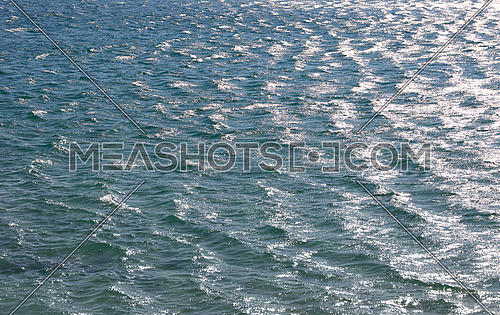 Blue sea water surface with ripples and waves, high angle view