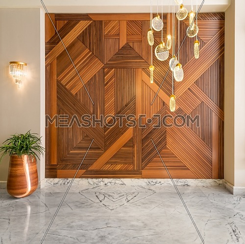 Hall with wood cladding wall decorated with geometrical patterns, tall rounded wooden planter with green bushes, contemporary glass LED tall chandelier, and white marble floor in modern house