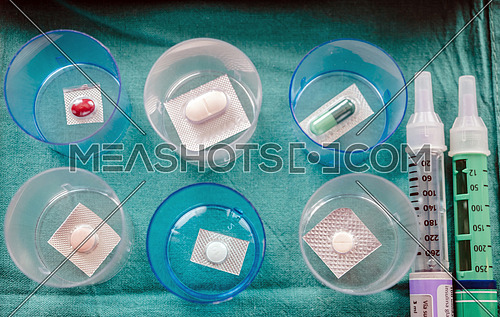 Diverse medication in glasses monodose along with insulin injectors in hospital, conceptual image, horizontal composition