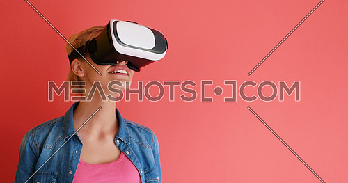 Happy girl getting experience using VR headset glasses of virtual reality, isolated on red background