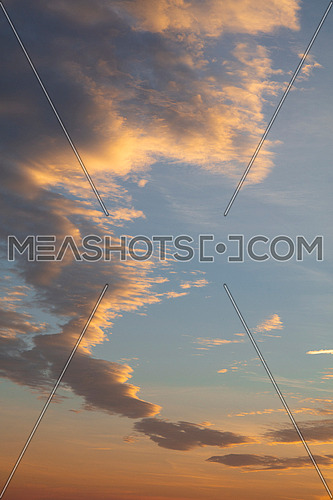 Beautiful dramatic cloudscape with orange and yellow fluffy sunset clouds over blue sky, low angle view