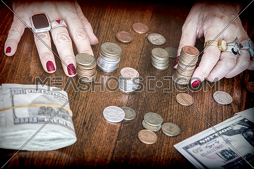 Women counting banknotes of dollar and some coins on a table, conceptual image