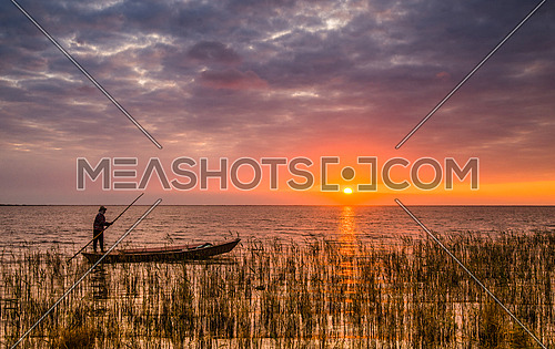 The fisher Man in his boat during sunset