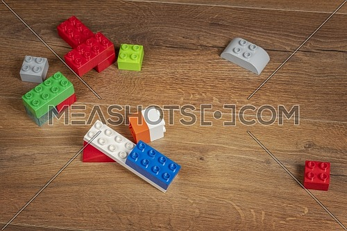 awesome view on colorful toy bricks on a brown wooden background. Toys in the table