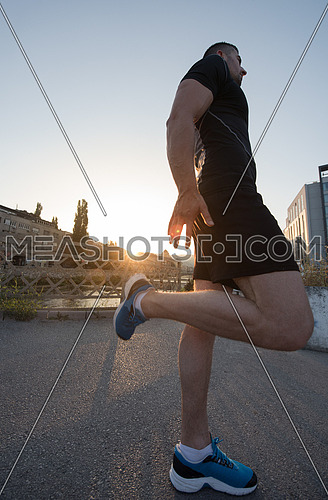 athlete man warming up and stretching while preparing for running on the city street at  sunny morning