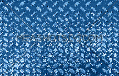 Close up background of dark blue toned industrial anti slip embossed metal steel plate with classic diagonal bumps of diamond pattern texture and black paint