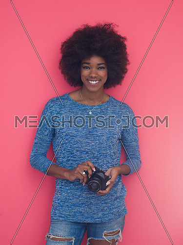 portrait of a smiling pretty african american girl taking photo on a retro camera isolated over pink background