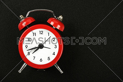 Time concept, small red metal alarm clock with red bells over black chalkboard background