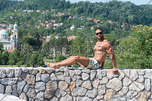 Smiling Athlete With Naked Torso Sitting And Resting On Rocks