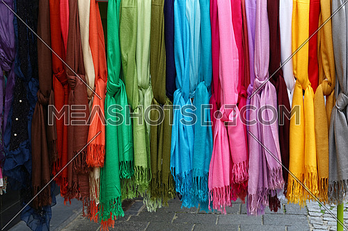 Close up selection of assorted colorful soft knitted scarves in apparel retail store display, low angle view