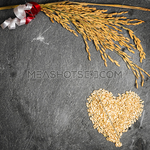 In the picture an ear of wheat and a heart formed by grains of rice on background of  stone.