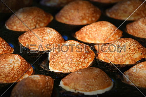 Close up of cooking small round Dutch traditional sweet pancakes, high angle view