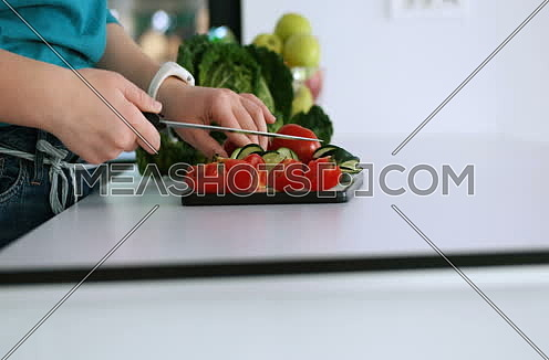 Close up of a young woman slicing tasty nutritious vegetables