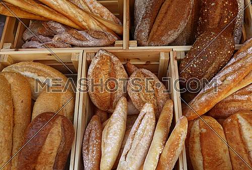 Close up several assorted fresh wheat bread loaves and baguettes in wooden box on retail display of bakery store, high angle view