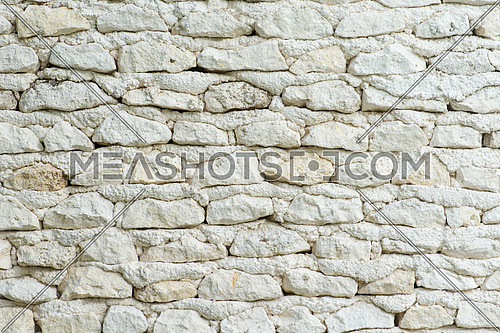 background of old white stone wall with one red brick