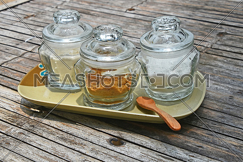 Three glass jars of different sugar, white and brown cane, on ceramic saucer with wooden spoon on old vintage bamboo table for coffee time