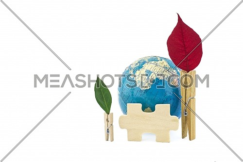 Conceptual ecology still life with world globe flanked by clothes pegs decorated with leaves and a wooden jigsaw puzzle piece over a white background with copy space