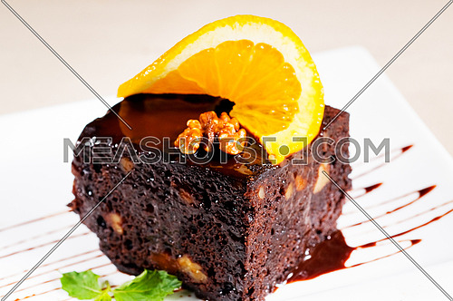 fresh baked delicious chocolate and walnuts cake with slice of orance on top and mint leaf