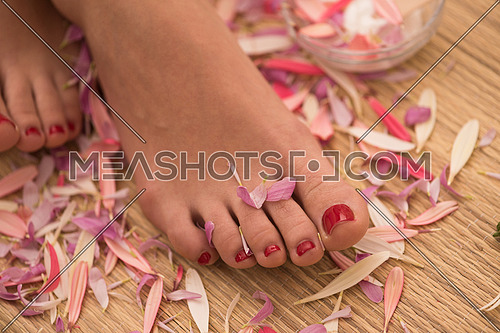 Closeup photo of a female feet at spa salon on pedicure and manicure procedure
