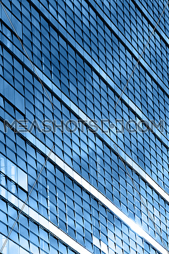 Blue glass windows of modern business office building, diagonal perspective, low angle view