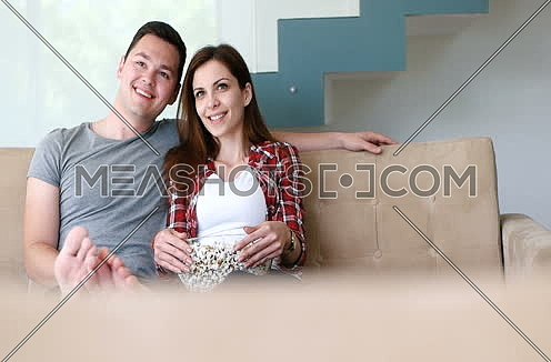 Couple eating popcorns and watching movie
