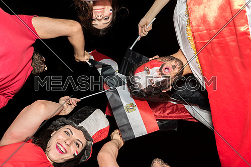 low angle for group of young people cheering for egypt, holding egyptian flags and drum while one of them has a paint egyptian flag on his face in the korba area at night