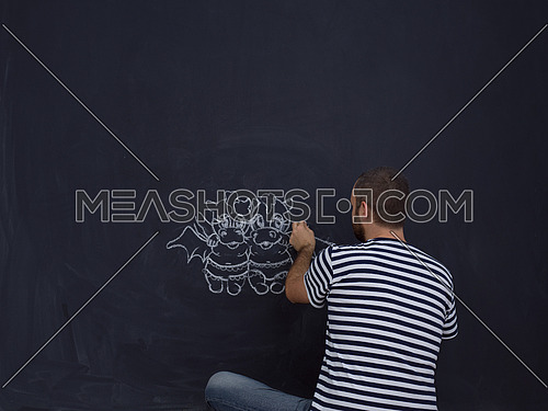 Conceptual photo of future dad drawing his imaginations about the future life with children on chalk board