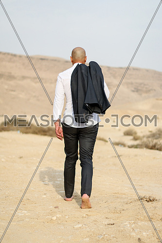 A man walking away alone in the desert business concept