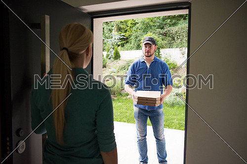 Pizza Delivery Man Giving Pizza Boxes To Smiling Young Woman