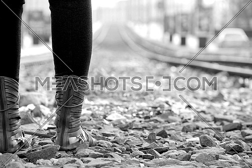 Girl wearing boots standing on stones shot from behind