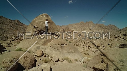 Follow shot for a male tourist wearing a white shirt exploring Sinai Mountain for wadi Freij at day.
