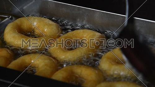 Close up deep frying several small round ring donuts in sizzling oil, high angle view