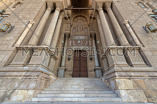 Entrance of al Rifai Mosque with closed decorated wooden doors, ornate columns, ornate recessed stone wall and stairs, Old Cairo, Egypt