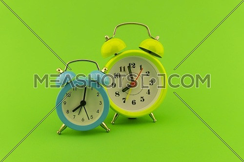 Blue and yellow twin bell analog alarm clocks over a colorful green background with copy space
