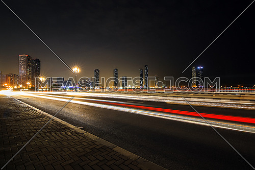 highway by night showing an urban modern cityscape and car lights in long exposure speed concept